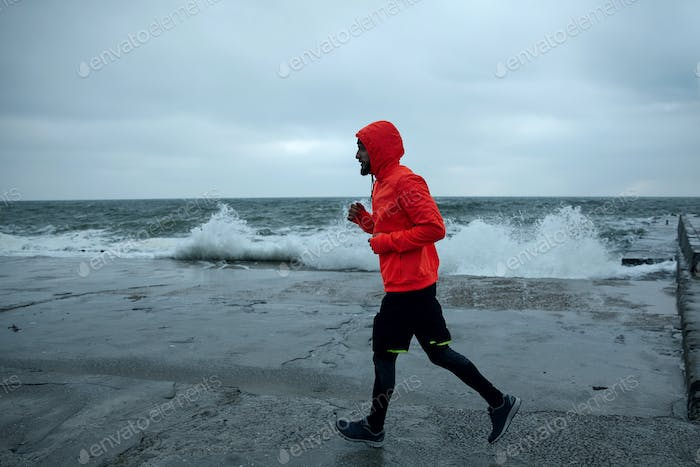 sportsman dressed in warm sporty clothes running over seaside on grey and stormy weather