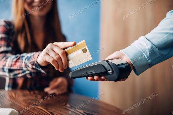 Young woman paying with credit card in cafe