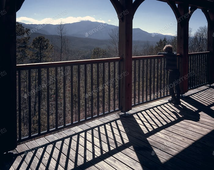 Boy on Porch in Mountains