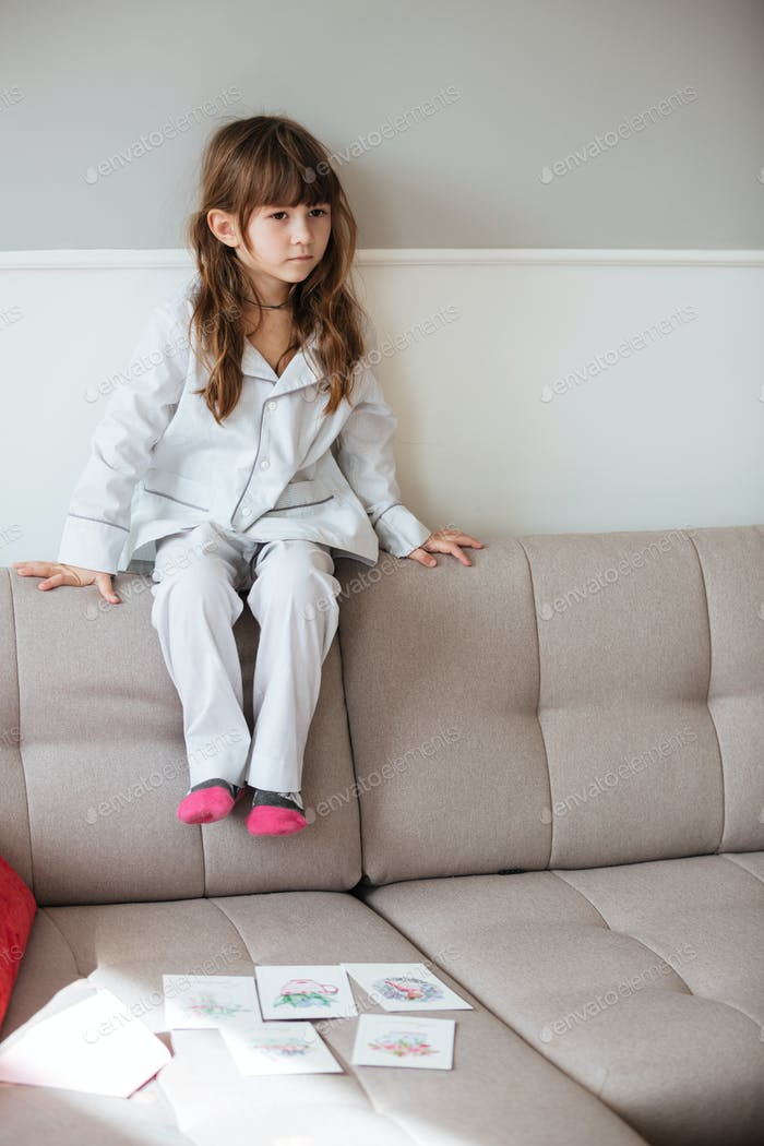 Little girl sitting on couch in living room