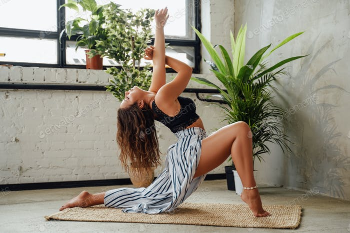 Woman relaxing and does yoga in light room