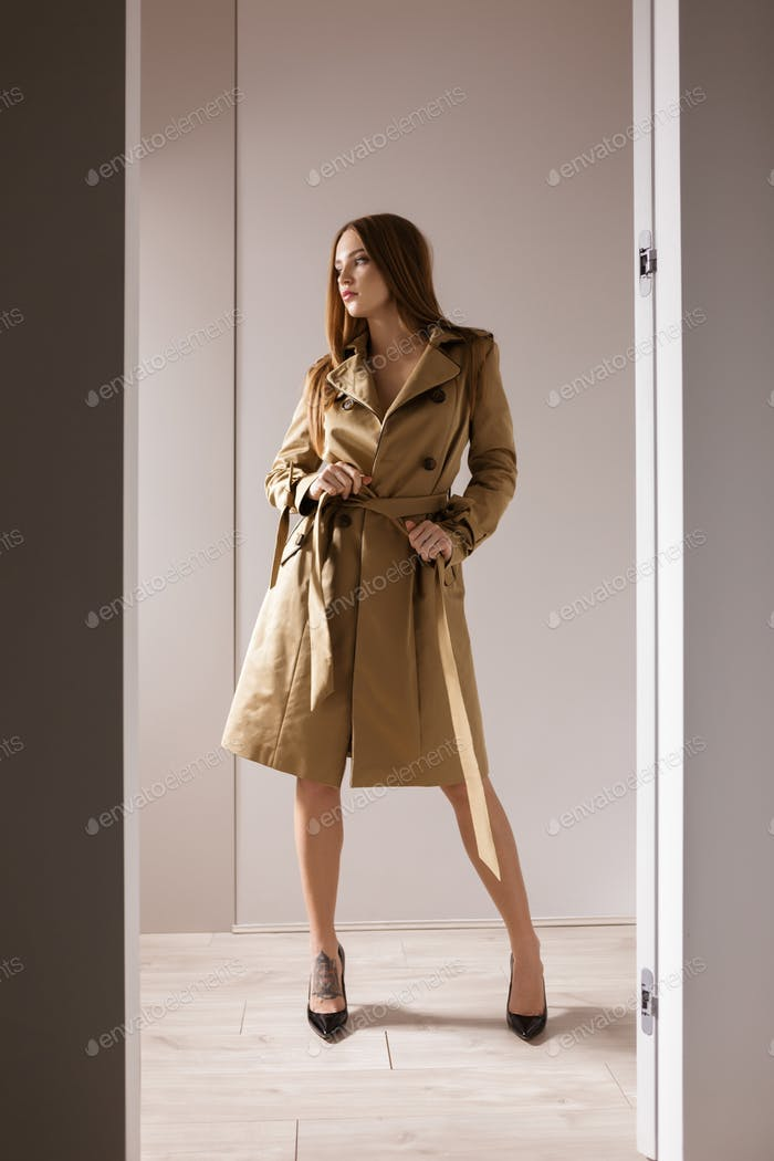 Beautiful lady in trench coat and black shoes on heels standing and dreamily looking aside