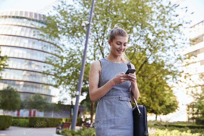 Businesswoman Walking To Work In City Looking At Mobile Phone