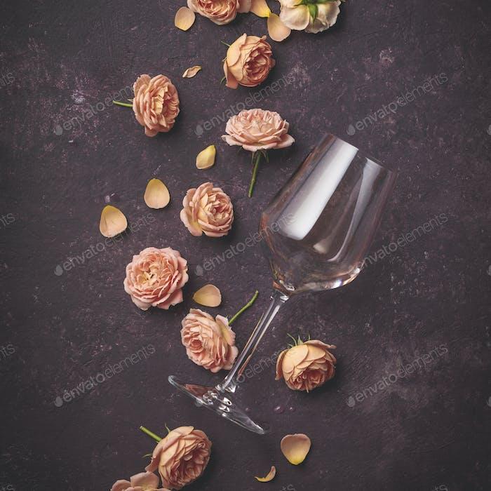 Rose wine and roses on dark purple background