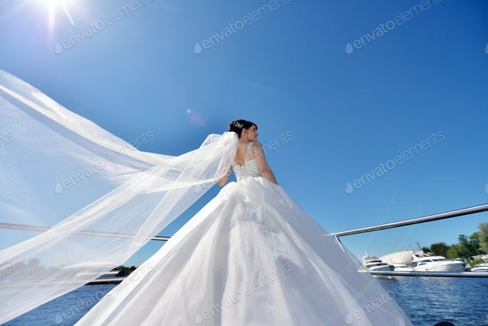 Beauty bride in bridal gown with lace veil on a yacht