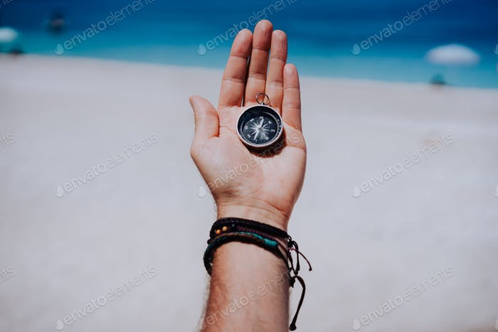 One open stretched hand palm with black metal compass on the sandy beach. Find your wish goal way