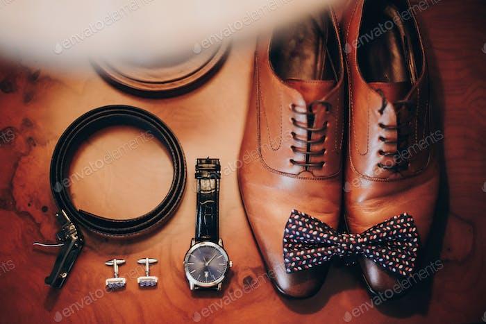 Stilvolle Uhr und teure braune Schuhe für den Bräutigam auf Holztisch im Hotelzimmer