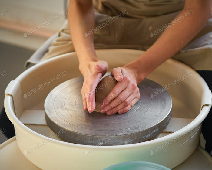 Woman making ceramic pottery on wheel, creation of ceramic ware. Concept for small business