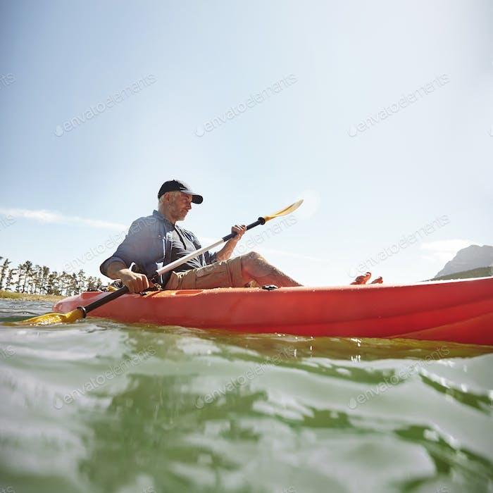 Mann Kajakfahren auf See im Sommer