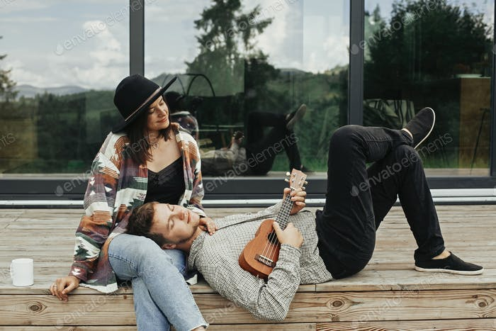 Happy hipster couple relaxing on wooden porch of modern cabin with big windows