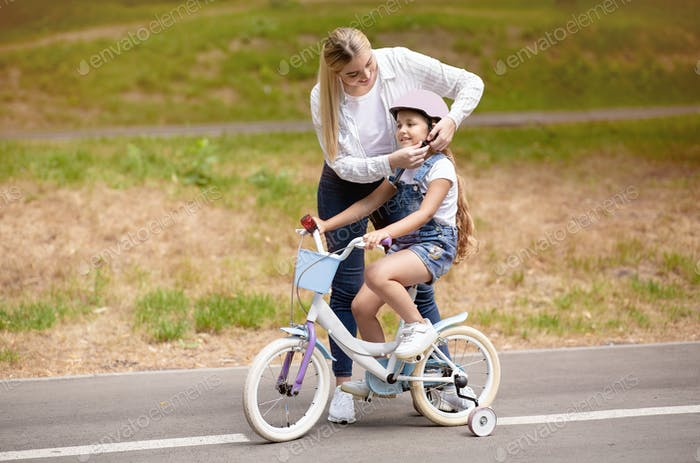 Mother Teaching Daughter To Ride Bike With Stabilisers Outside