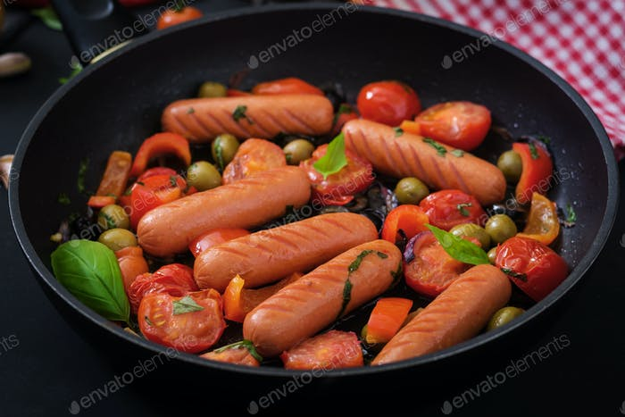 Sausages grilled with vegetables in the Greek style on pan.
