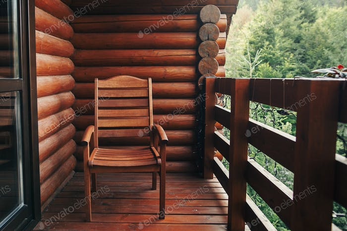 Wooden chair on porch of cabin among woods