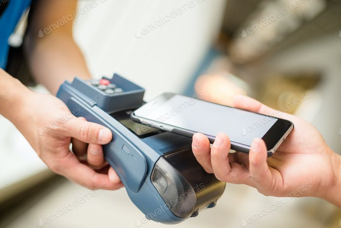 Kunde nutzt Handy für Bezahlung durch NFC-Technologie