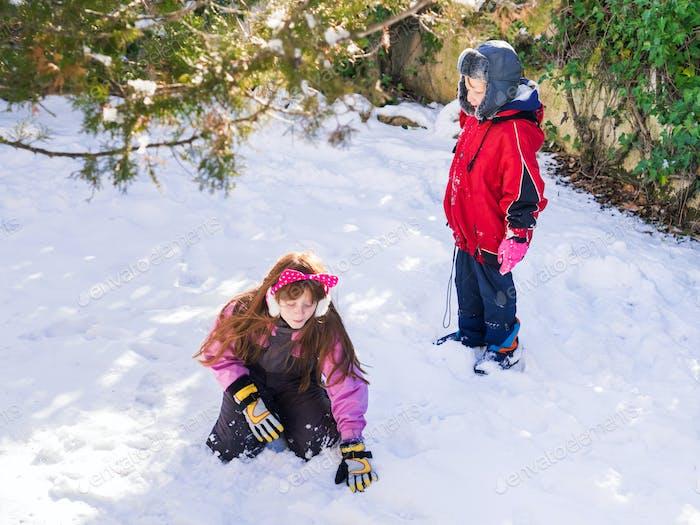 Смешные братья и сестры играют зимой со снегом