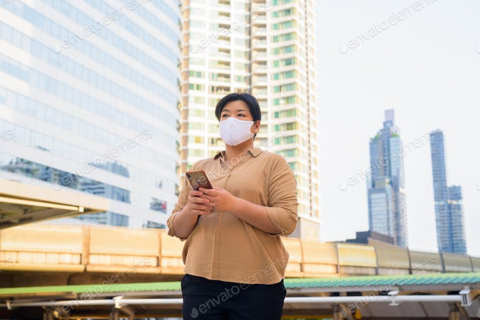 Overweight Asian woman with mask thinking while using phone at skywalk bridge