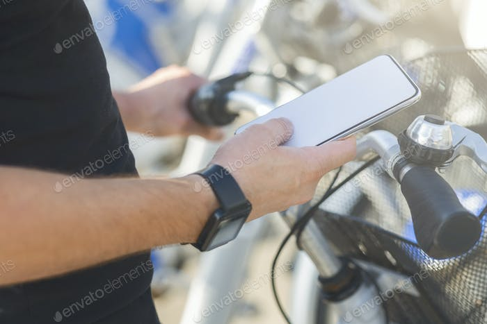 Man browsing on cellphone during bicycle ride in city