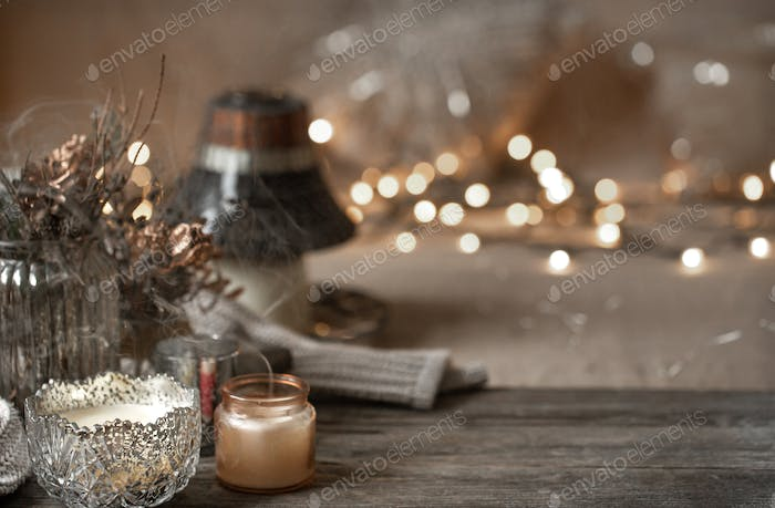 Cozy winter background with details of home decor on a blurred background with lights copy space.