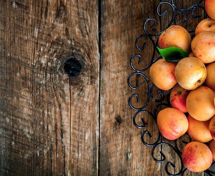 Schüssel mit geernteten Aprikosen. Frische Aprikosen auf hölzerner Backgroun