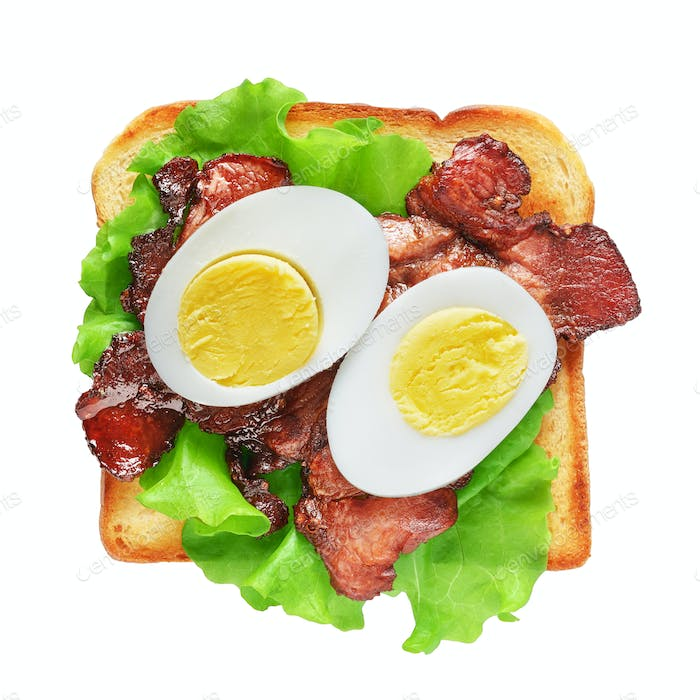 Toasted sandwich bread with bacon, lettuce and eggs isolated