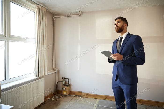 Male Realtor With Digital Tablet Carrying Out Valuation On Property For Renovation