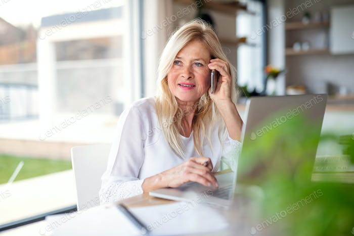 Senior woman with smartphone and laptop indoors in home office, working