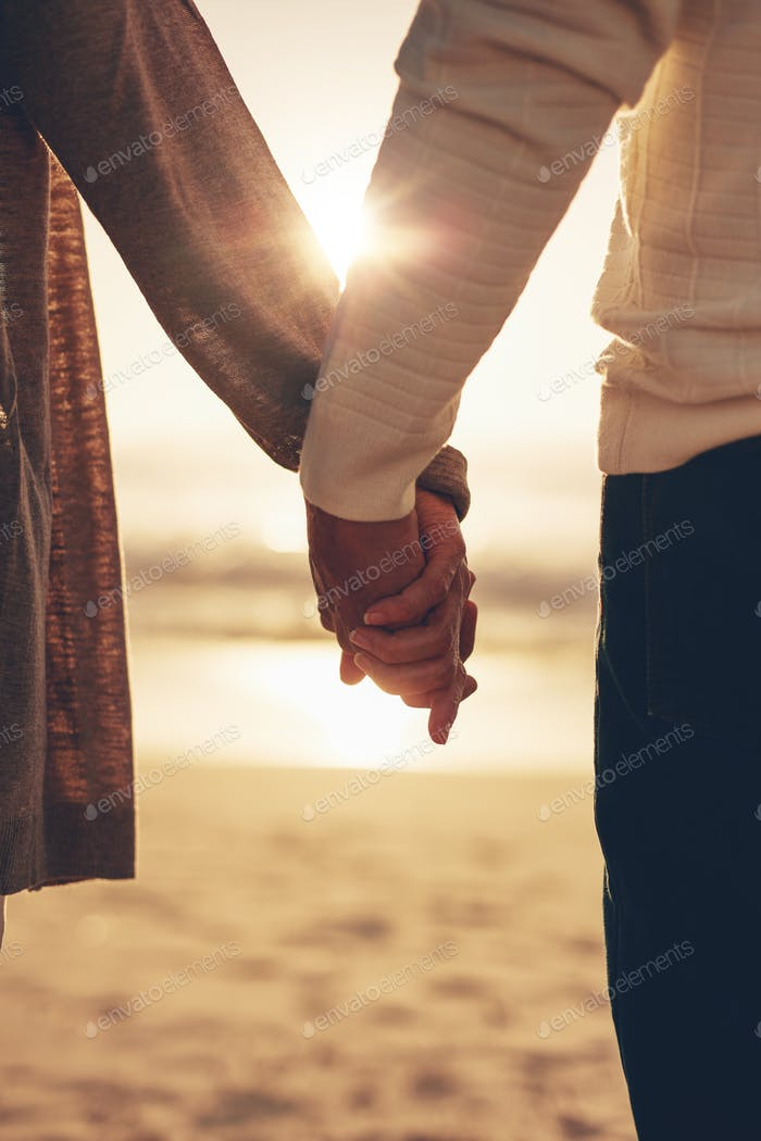 Senior couple holding hands on the beach at sunset