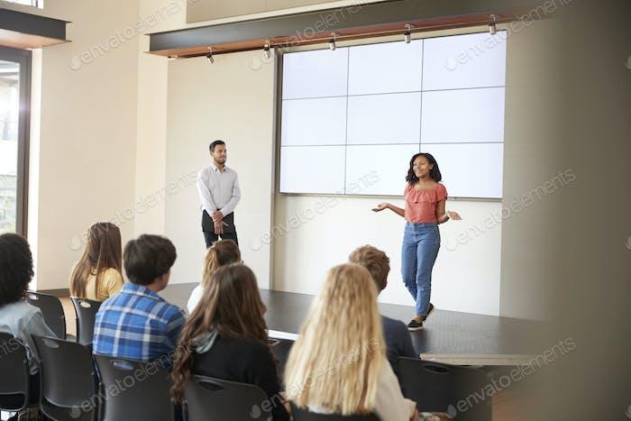 Weibliche Studentin geben Präsentation zu High School Klasse vor dem Bildschirm