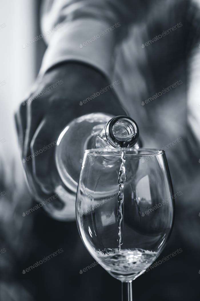 Pouring white wine from bottle