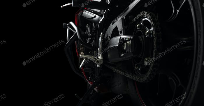 Side view of red sports motorcycle in a spotlight on a black background