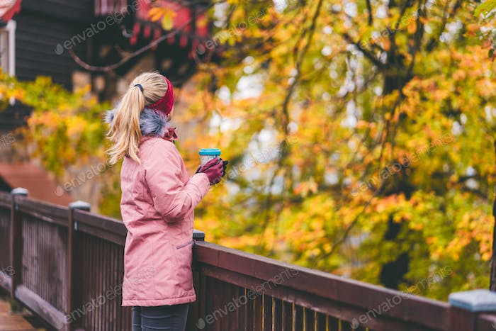 Adult blond woman holds a cup of herbal tee in hands on wooden bridge with beautiful golden autumn