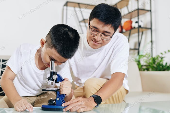 Dad showing microscope to son