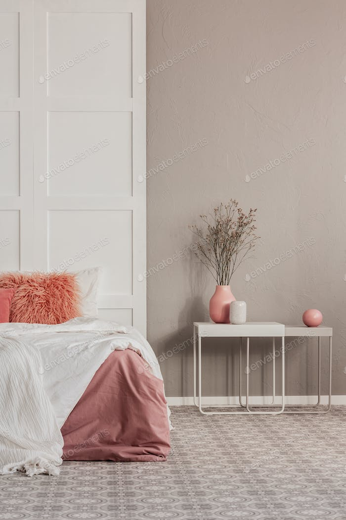 Copy space on grey wall of elegant bedroom interior with white table and king size bed