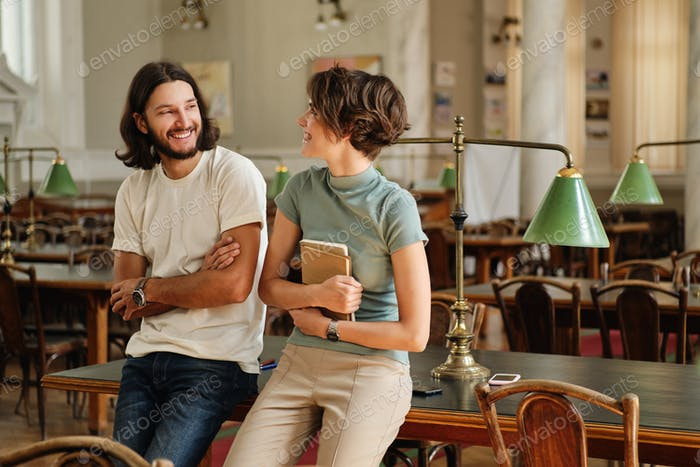 Young attractive smiling casual students with notepad joyfully talking in library of university