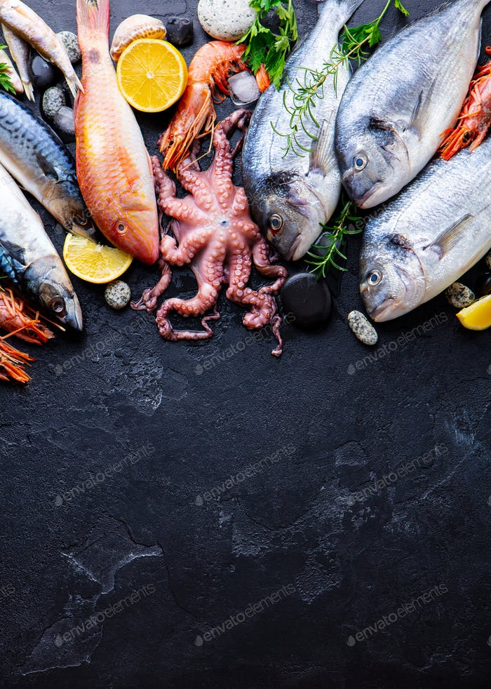 Frisches Fisch- und Meeresfrüchte-Sortiment auf schwarzem Schiefer-Hintergrund. Draufsicht. Leerzeichen kopieren.