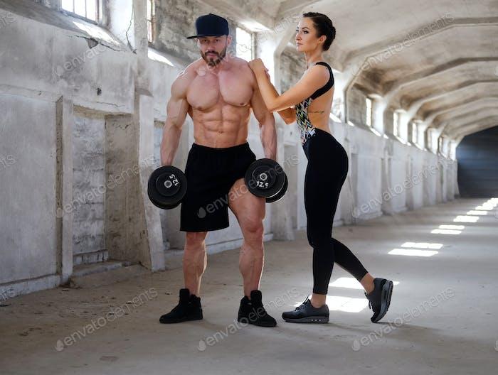 Tolles Fitness-Paar posiert in großen Industriehalle.