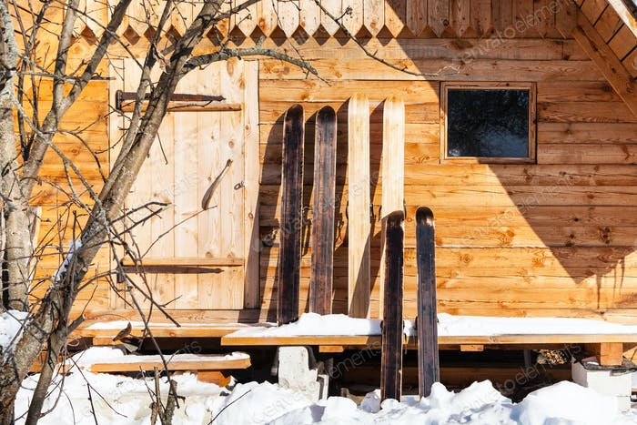 wide hunter skis in front of wooden cottage