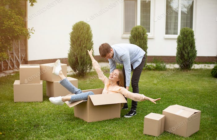 Young family enjoying moving day, being silly together in front yard of their new home