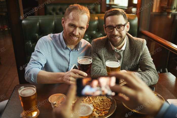 Men posing at camera in the pub