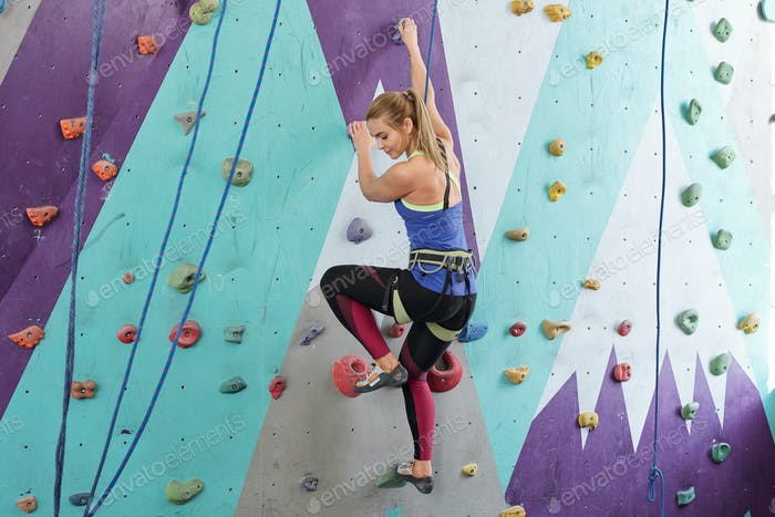 Young active female in sportswear holding by multi-color rocks on climbing wal