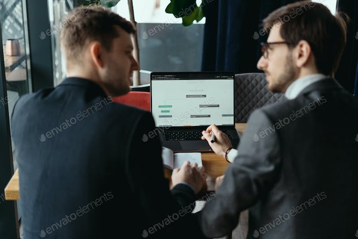 Two young businessman having a successful meeting at restaurant.