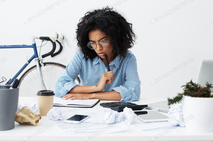 Concentrated female marketing expert holding pen, looking thoughtful while working over new business