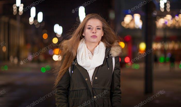 Hermosa mujer por la noche en la ciudad