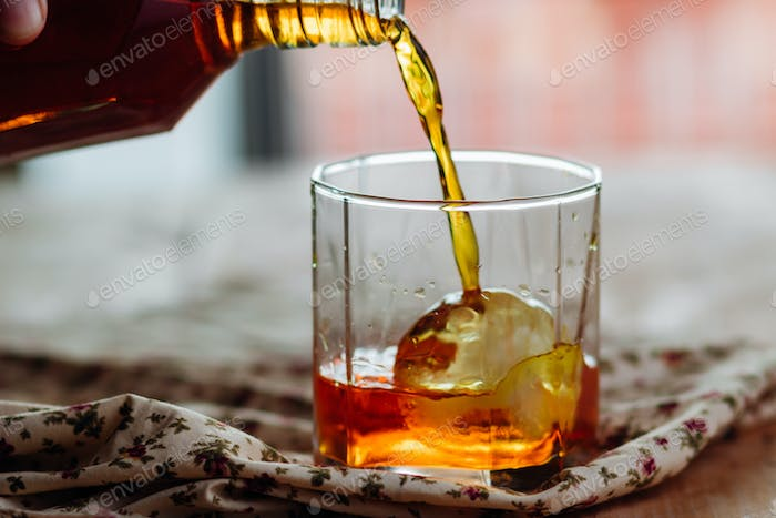 Pouring brandy into a glass of on the rock