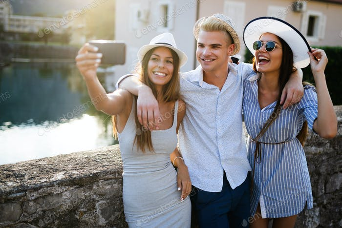 Group of happy friends enjoying sightseeing tour in the city