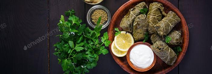 -  Dolma. Gefüllte Traubenblätter mit Reis und Fleisch auf dunklem Tisch. Küche aus dem Nahen Osten.