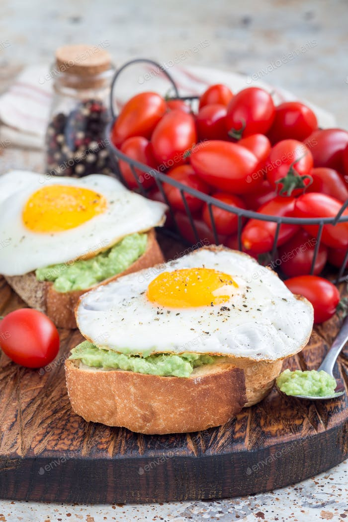 Open sandwich with mashed avocado and fried egg, sprinkled with black pepper, vertical