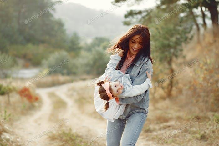 Mutter mit kleiner Tochter spielen in einem Herbstfeld
