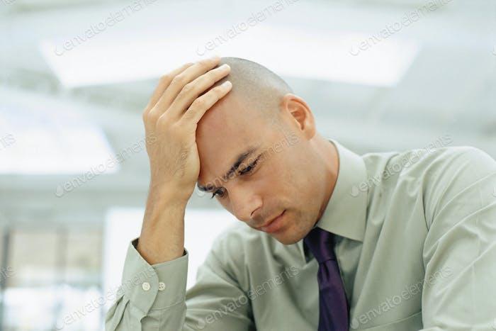 Black businessman rubbing his head