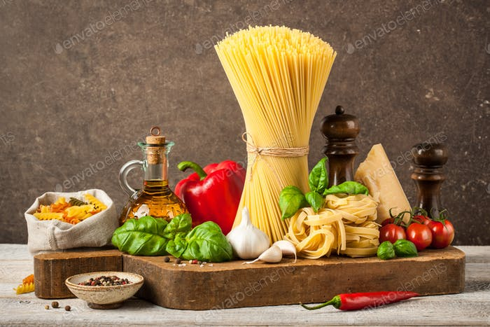 Pasta, spaghetti and ingredients on wooden table